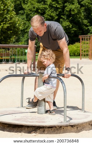 Dad and son playing on merry-go-round on playground - stock photo