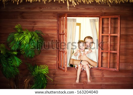 Dad and son sitting on the window - stock photo
