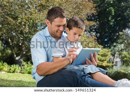 Dad and son using a tablet pc in a park on sunny day - stock photo