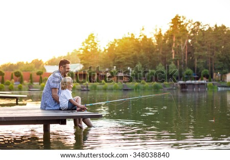 Dad and son with fishing rods - stock photo