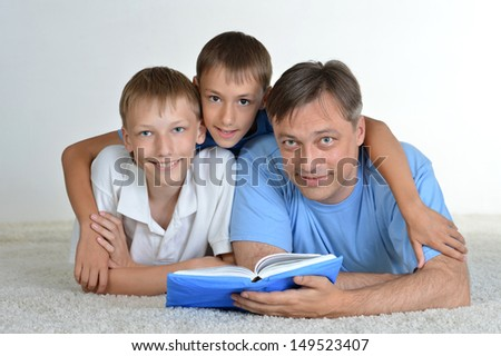Dad and sons reading a book on the floor