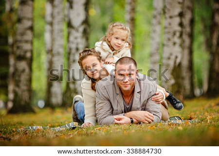 Dad and two charming sisters in the same curly beige knitted sweater, family, lie on a striped rug and a smile on the background of yellow leaves in autumn