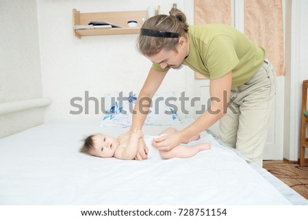 Dad changing diaper on baby girl on bed, changing nappy, everyday care