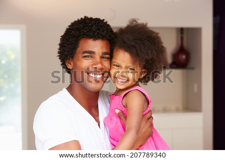 Dad Cuddling Daughter At Home - stock photo