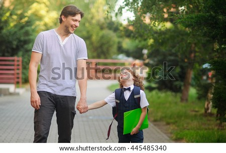 Dad escorted to school by his son. The tall man tightly holding the hand of small disciple. Father and son with love and tenderness look at each other and something fun to talk.