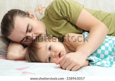 Dad gently kissing daughter. Little child baby lying with daddy and preparing to sleep