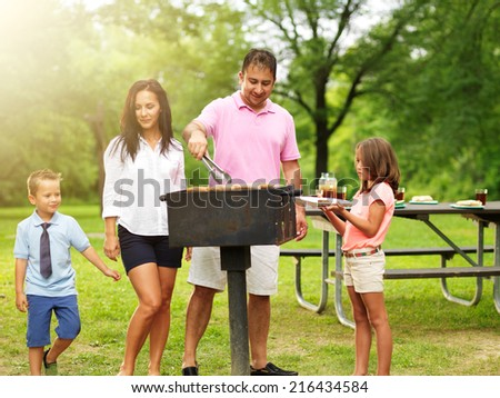 dad grilling food for wife and kids at outdoor cookout - stock photo