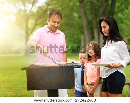 dad grilling food for wife and kids at outdoor cookout shot with selective focus and lens flare