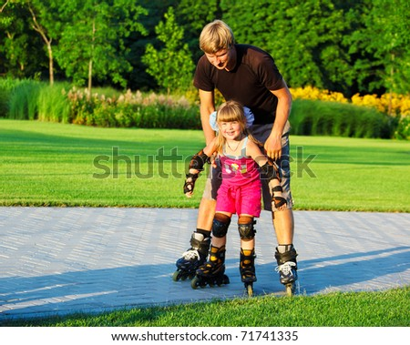 Dad helping daughter with her first rollerskates - stock photo