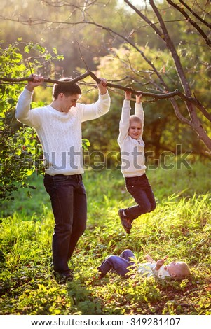 Dad helps support the boy hanging on the branch of a tree, autumn, sunset, summer
