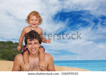 Dad holding his kid on the shoulders both laughing and looking at camera - stock photo