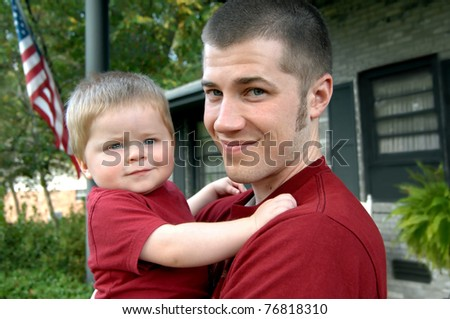 Dad holds his son as they stand outside their home.  Both are dressed in burgundy tee shirts.  Father is grinning and baby is too. - stock photo