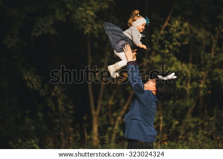 Dad in the park playing with her baby by throwing daughter up, Dad and daughter dressed like a fairy tale Alice in Wonderland, Dad and daughter happy family laughing - stock photo