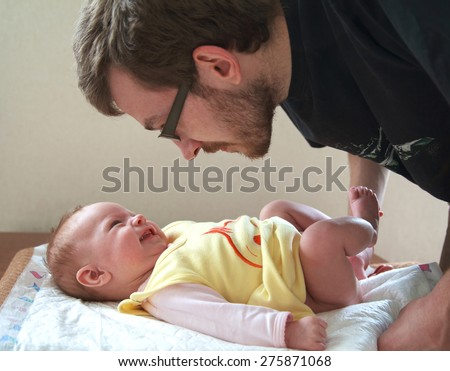 Dad is going to change a diaper to his small smiling baby, selective focus - stock photo