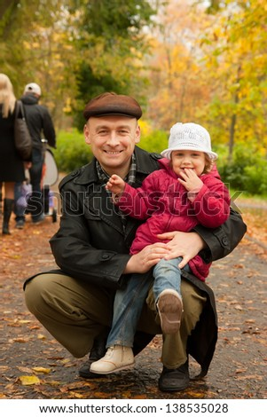 Dad is holding his daughter in his arms in autumn park