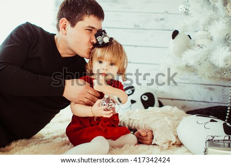 Dad kissing daughter near Christmas tree - stock photo