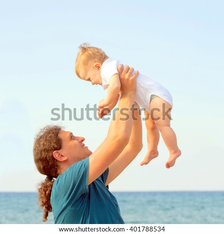 Dad playing with baby and holding up kid on the beach. Father's day, happiness and people concept