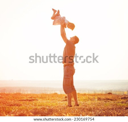 Dad playing with baby daughter in a field at sunset - stock photo