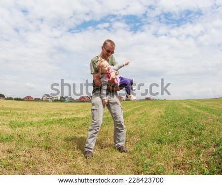 Dad playing with his baby daughter, he turns her around himself, selective focus, the effect of motion and fisheye ( perspective) - stock photo