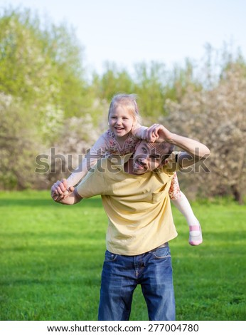 Dad playing with his baby daughter in a pink dress, carrying her on his back, selective focus  - stock photo