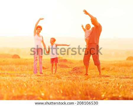 Dad playing with his daughter in a field at sunset - stock photo