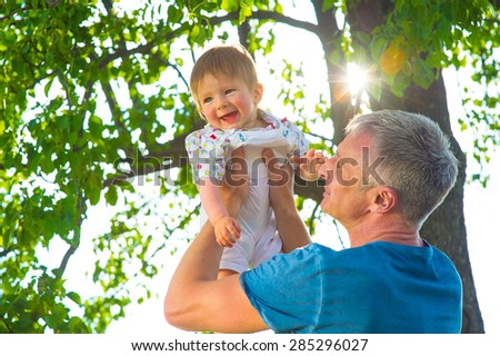 Dad playing with his son in the garden. Man with  baby.