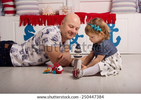 Dad plays with daughter in sea sailor interior. Carefree childhood, game, entertainment, parenting - stock photo
