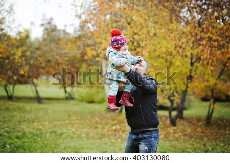 Dad plays with her little daughter in the autumn Park, he lifts her up, the girl laughs, the fall, there are a lot of yellow leaves. - stock photo
