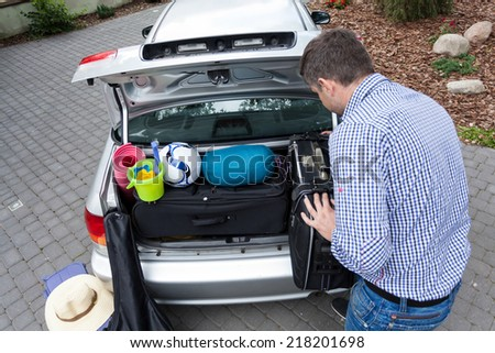 Dad preparing car trunk for holiday, horizontal - stock photo