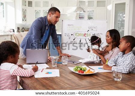 Dad presenting domestic meeting to his family in the kitchen - stock photo
