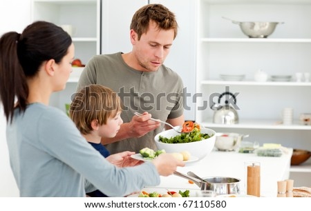 Dad serving salad to his family for lunch in the kitchen - stock photo