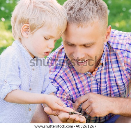 Dad showing to his son a dragonfly.