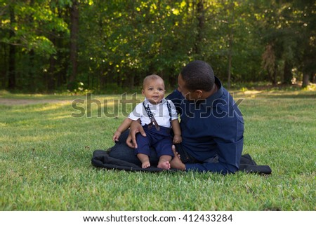 Dad sitting with his baby out in the grass