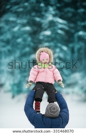Dad throws daughter with Down syndrome in the winter forest - stock photo