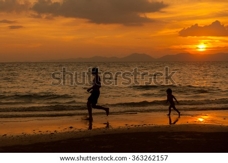 Dad with a child running along the beach during sunset