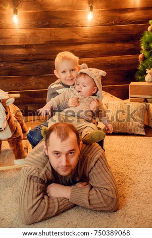 dad with children playing by the fireplace and Christmas tree