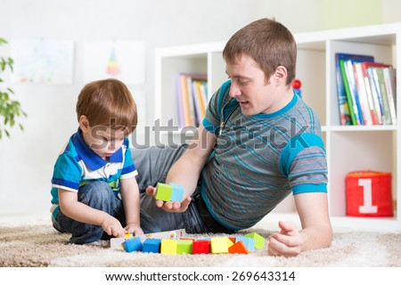 dad with his son child play together at home - stock photo