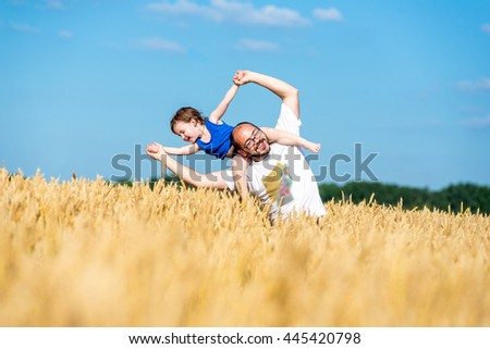 Dad with his son in a wheat field. father and son having fun outdoor in wheat field - stock photo