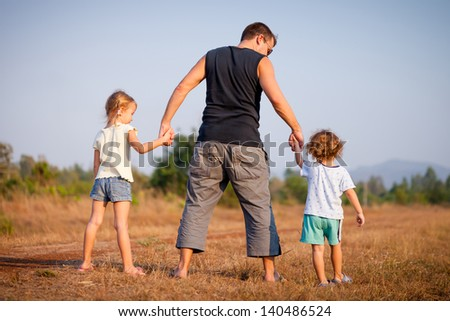 Dad with kids walking on the road - stock photo