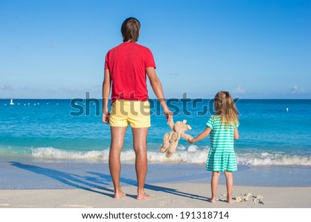 Dad with little baby holding a plush toy on exotic beach - stock photo