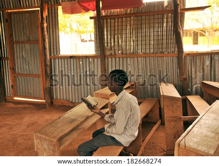 DADAAB, SOMALIA - AUGUST 7: Unidentified child in the class who read the Qur'an on August 7, 2011 in Dadaab, Somalia. Thousands of Somalis in refugee camps under very difficult conditions lives - stock photo