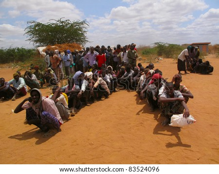 DADAAB, SOMALIA-AUGUST 15: Unidentified men and children wait for relief aid in the Dadaab refugee camp where thousands of Somalis end up due to hunger on August 15, 2011 in Dadaab, Somalia. - stock photo