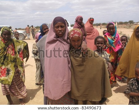 DADAAB, SOMALIA-AUGUST 15: Unidentified woman & children live in the Dadaab refugee camp where thousands of Somalis wait for help because of hunger on August 15, 2011 in Dadaab, Somalia. - stock photo
