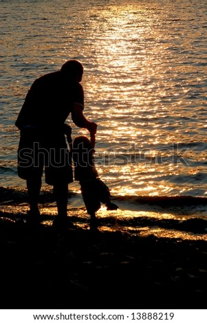 Daddy and boy at beach - stock photo
