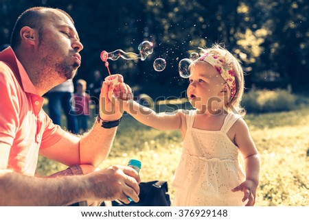 daddy and daughter blowing a bubbles in the park - stock photo