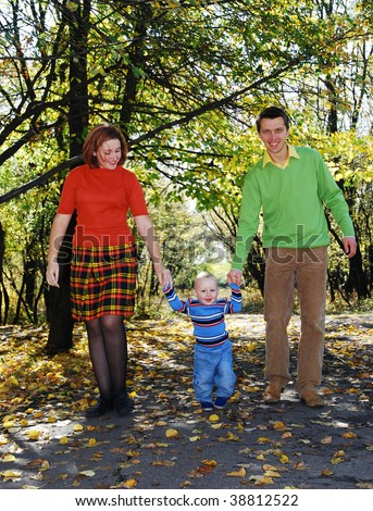 daddy and mom with  their little son  walking through the park in autumn