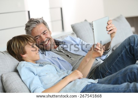 Daddy and son websurfing on digital tablet at home - stock photo