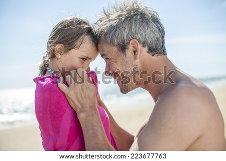 daddy at the beach wrapping his little girl in a towel after bath