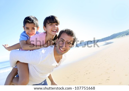 Daddy carrying children on his back at the beach - stock photo