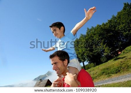 Daddy carrying son on his shoulders - stock photo